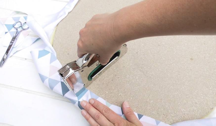 Agrafer le tissus sur la galette de bois, de manière à ce qu'il n'y ait aucun pli.