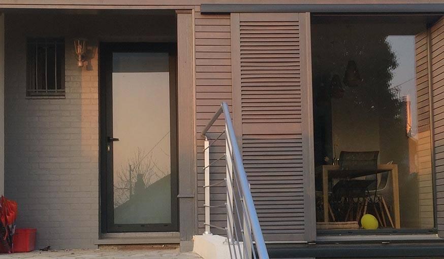 La façade modernisée allie verre, bois et de briques dans les tons gris.