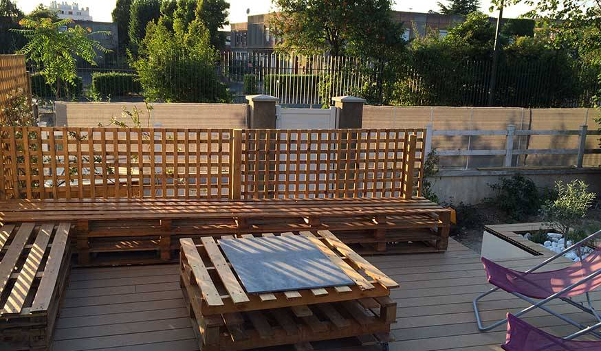 La terrasse après travaux, avec des bancs et une table sur roulettes fabriquées en palettes.