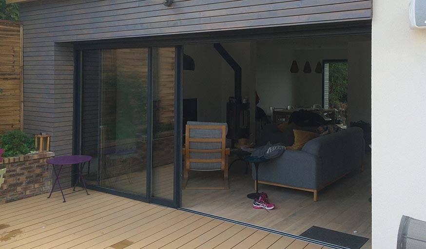 Un bardage en bois gris encadre la nouvelle porte-fenêtre.