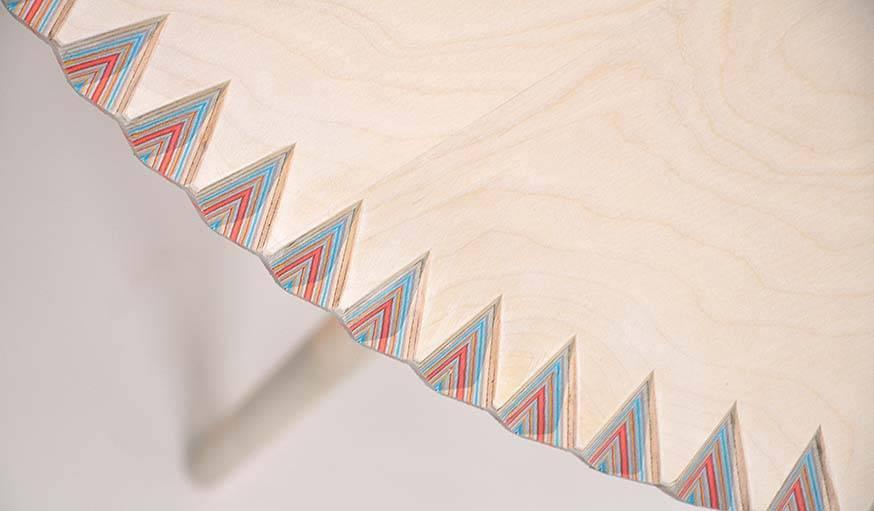 Les découpes sur la tranche de la table permettent d'admirer les feuilles de papier superposées.