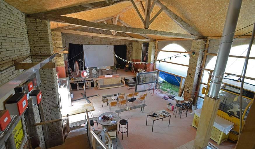 La grange de Lîlegal. Sur la scène, un rétroprojecteur servira d'écran au rétroprojecteur pendant le rassemblement des artisans poêliers.