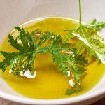 Une feuille de citronnelle repose dans de l'huile pour faire un anti moustique naturel et fait maison