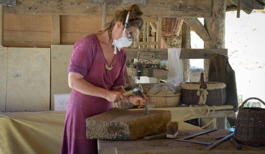 Une tailleuse de pierre, travaillant avec des outils d'époque mais équipée d'un matériel de protection.