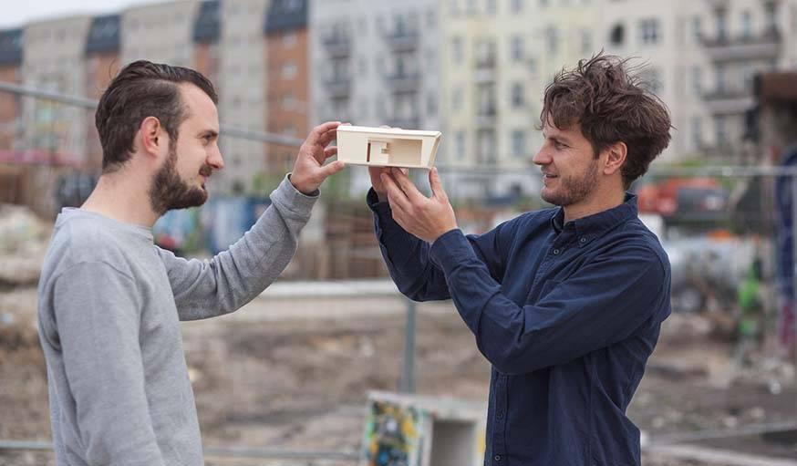 Les deux architectes montrant leur projet.