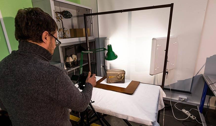 Un bénévole d'Emmaüs photographiant un objet mis en vente sur le site.