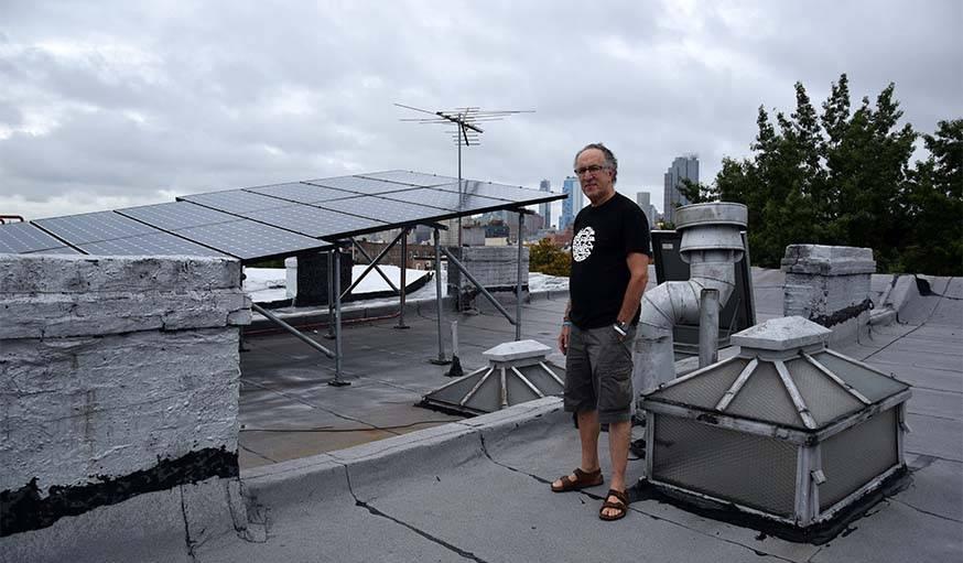 Eric Frumin devant ses panneaux solaires, et en arrière-plan, New-York.