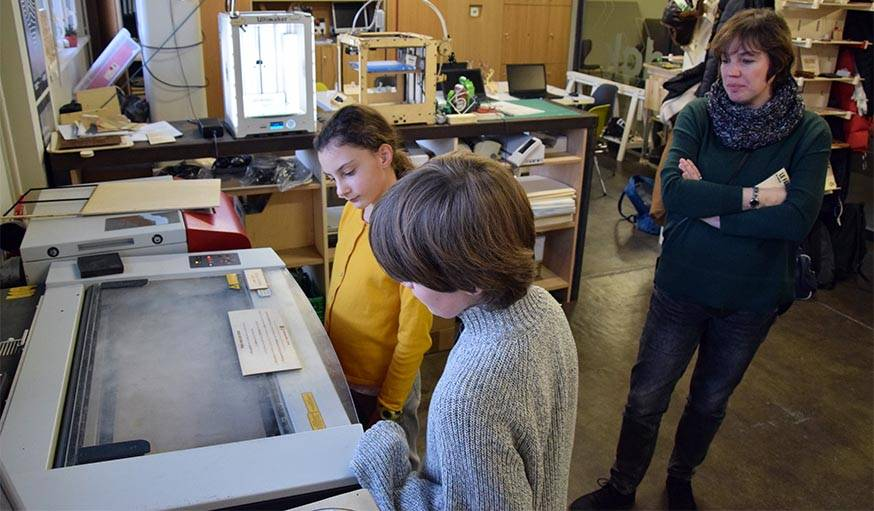 Tom et Lola observent le travail de la découpeuse laser.
