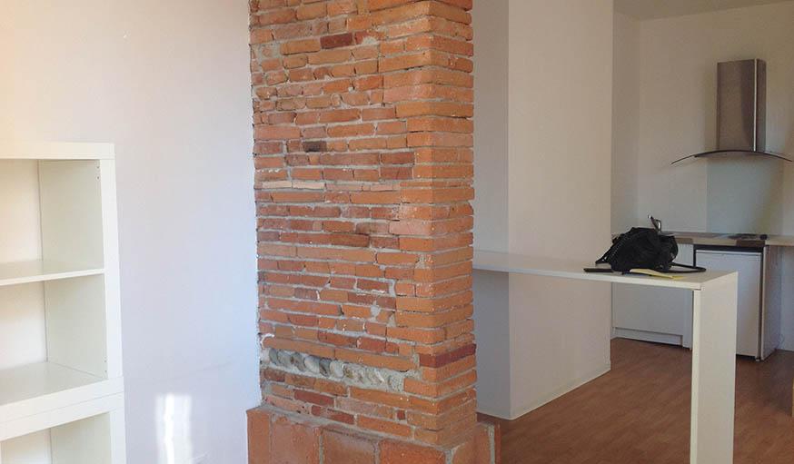 Le coin repas et la cuisine derrière l'arche en briques, avant les travaux.