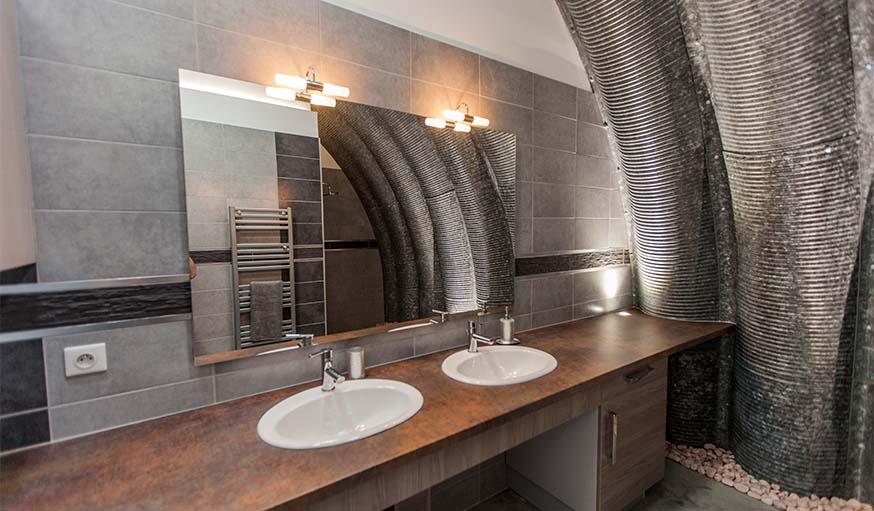 Dans cette salle de bains, la voûte en acier imprime son style.