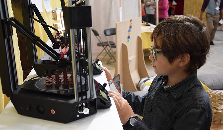 Gaël, 10 ans, observe l'impression en 3D des boulons OpenFabrick.