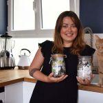 """Louise Salvati pose dans sa cuisine avec ses """"poubelles"""". Chaque bocal contient plusieurs mois de déchets non recyclables."""
