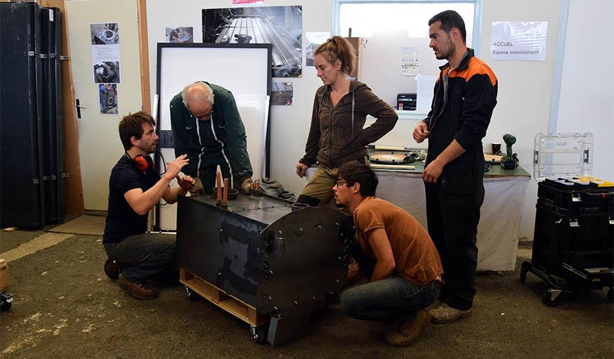 Samuel Le Berre (tout à gauche) réfléchit avec les stagiaires au meilleur moyen de déplacer ce poêle.