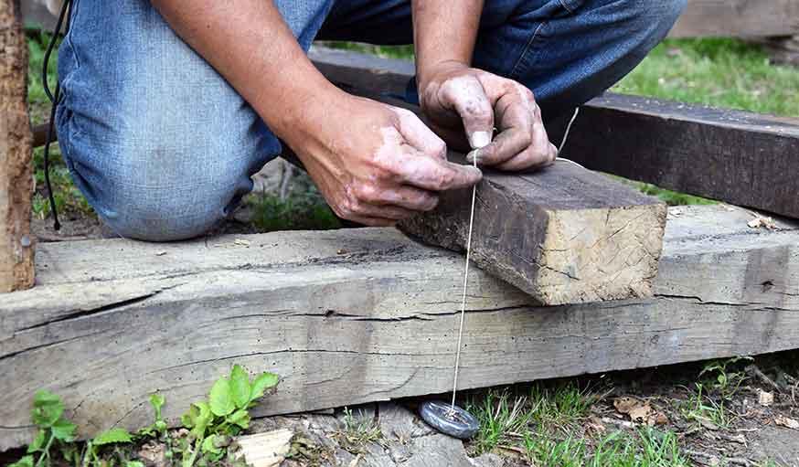 Le fil à plomb permet de tracer des repères sur le bois.