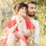 Un couple qui s'enlace dans l'herbe au coucher du soleil
