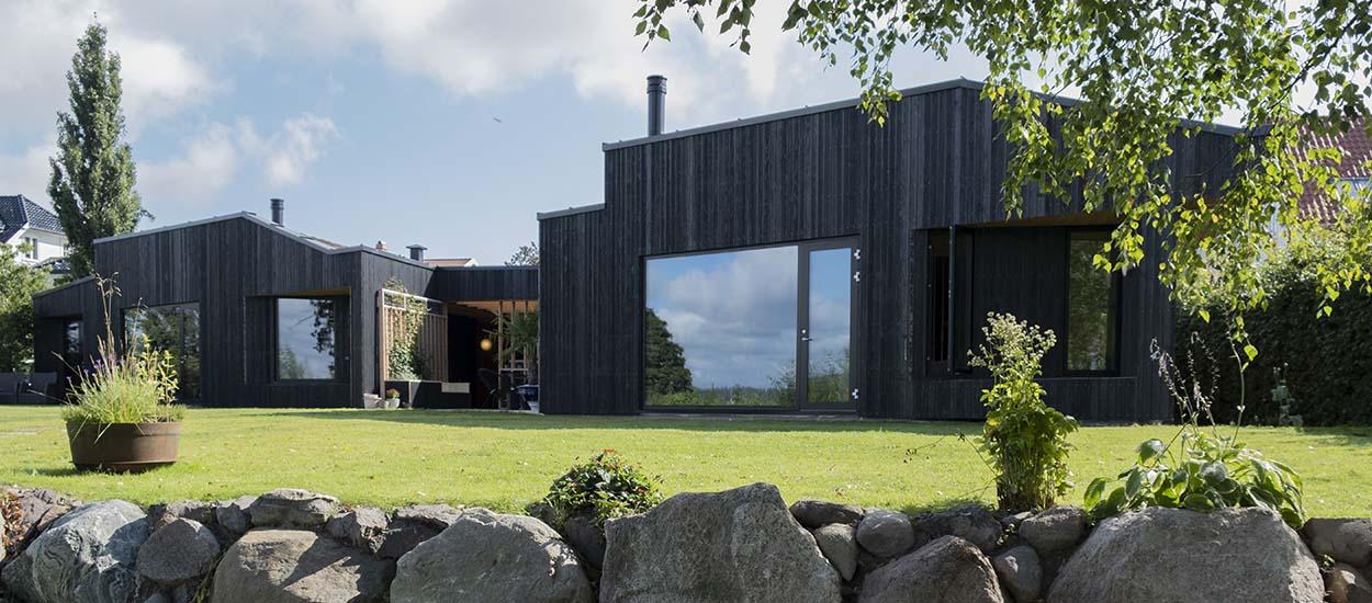 Tout seul, il construit sa maison moderne en bois brûlé