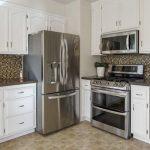 photo d'une cuisine américaine mal conçue avec frigifaire, four, et des placards