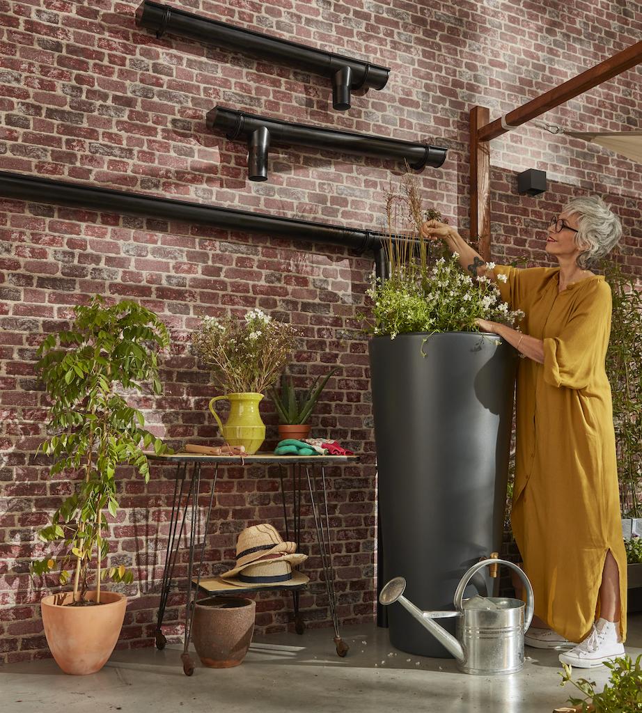 femme qui jardine sur un potager avec récupérateur d'eau