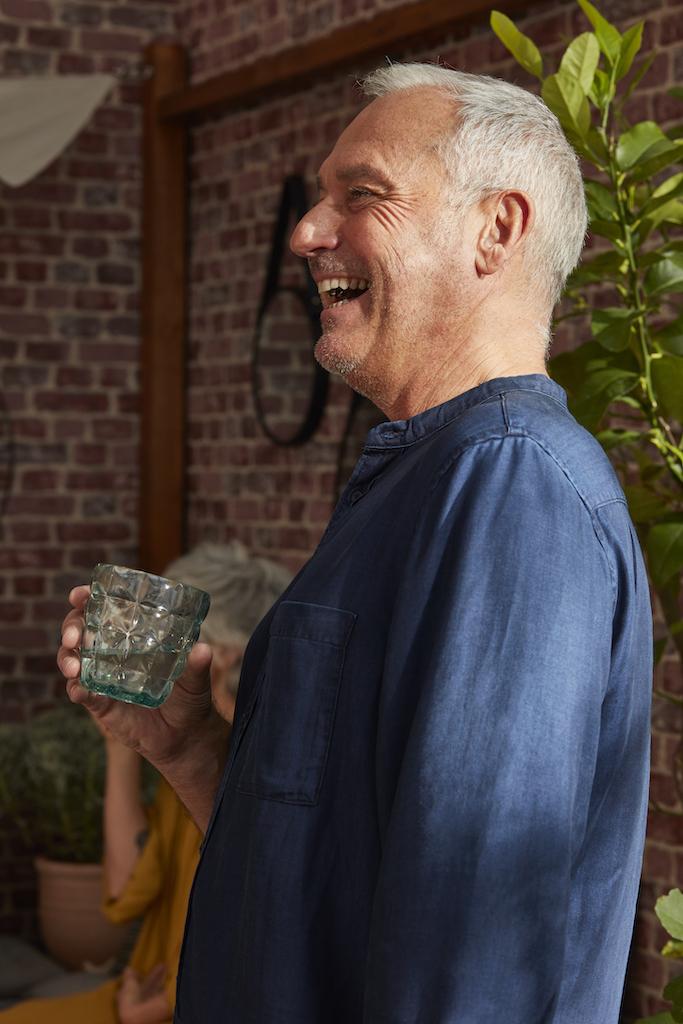 homme avec un verre qui rigole