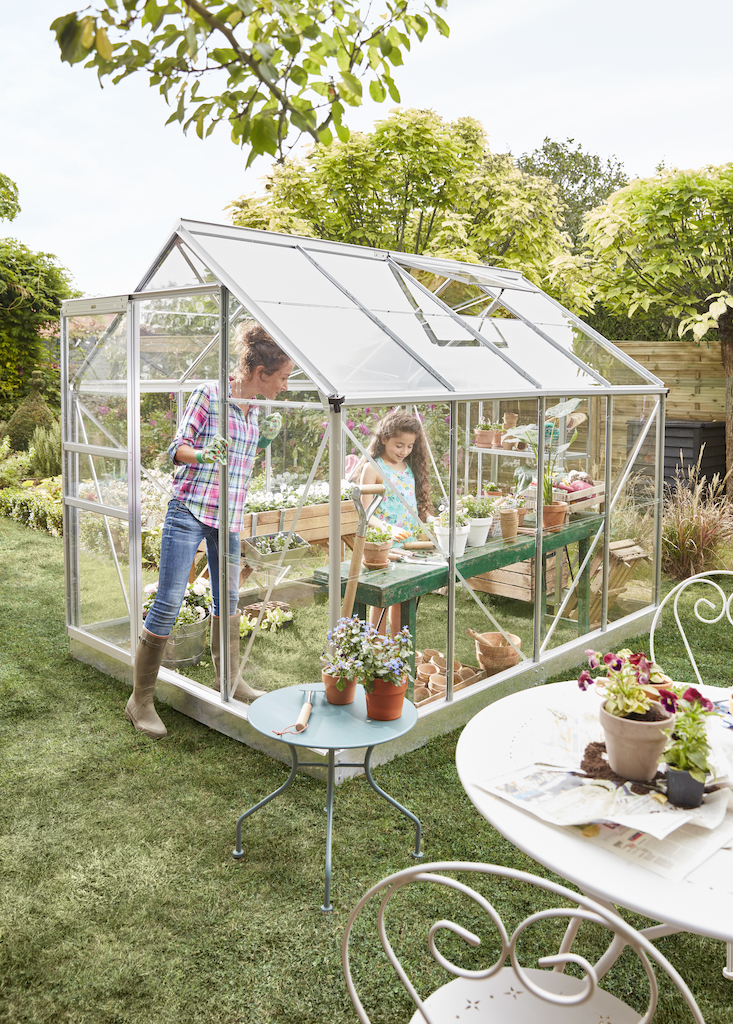 Serre avec mère et fille qui jardinent