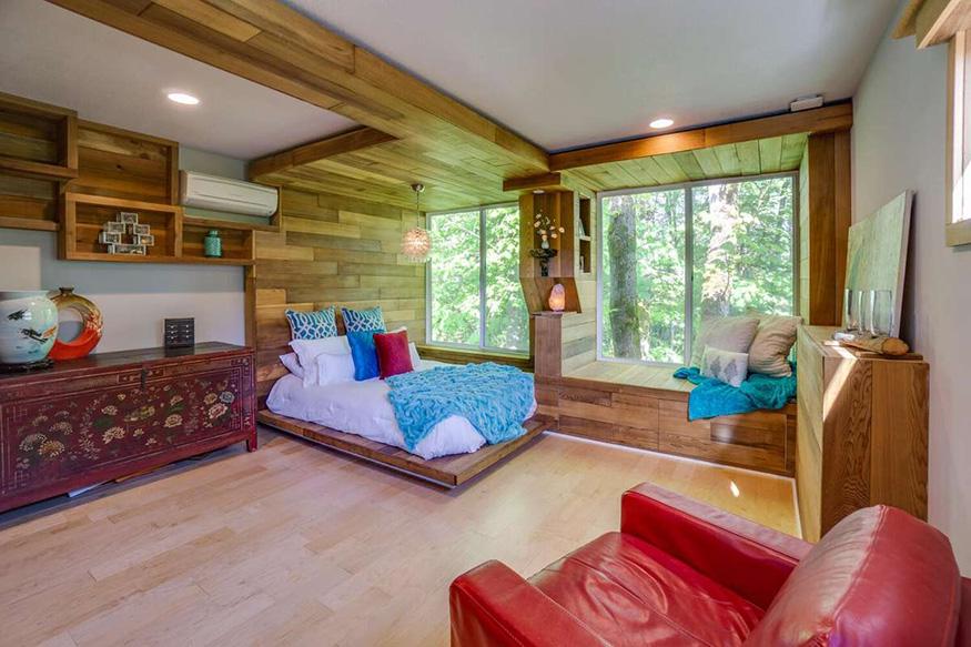 Une chambre en bois avec vue sur des arbres