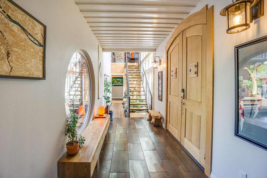 Une entrée avec une porte en acajou et une fenêtre ronde