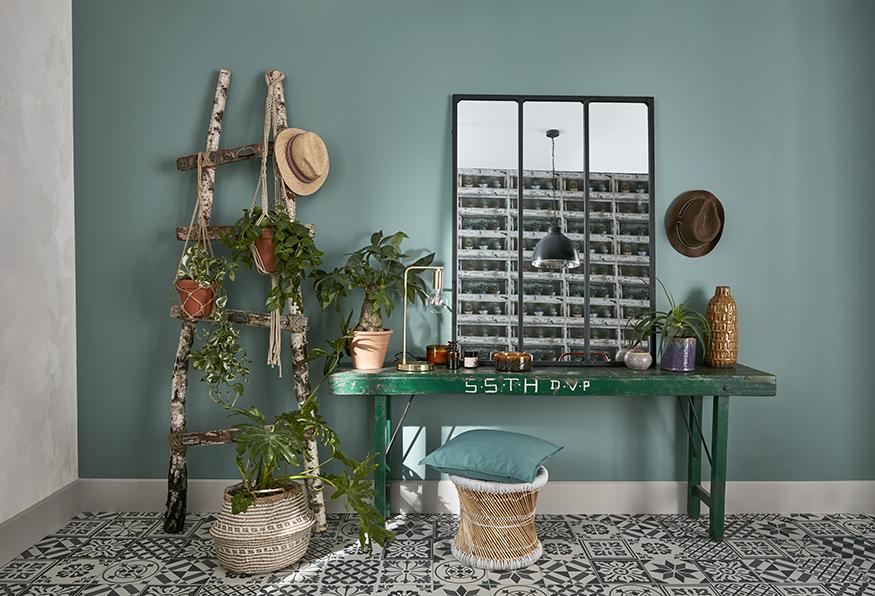 une échelle fabriquée en branches dans le coin d'une pièce avec un banc et un miroir