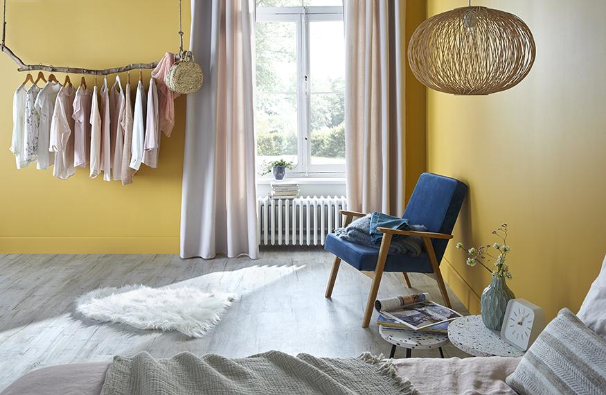 Un dressing dans une chambre réalisé avec une branche d'arbre suspendue