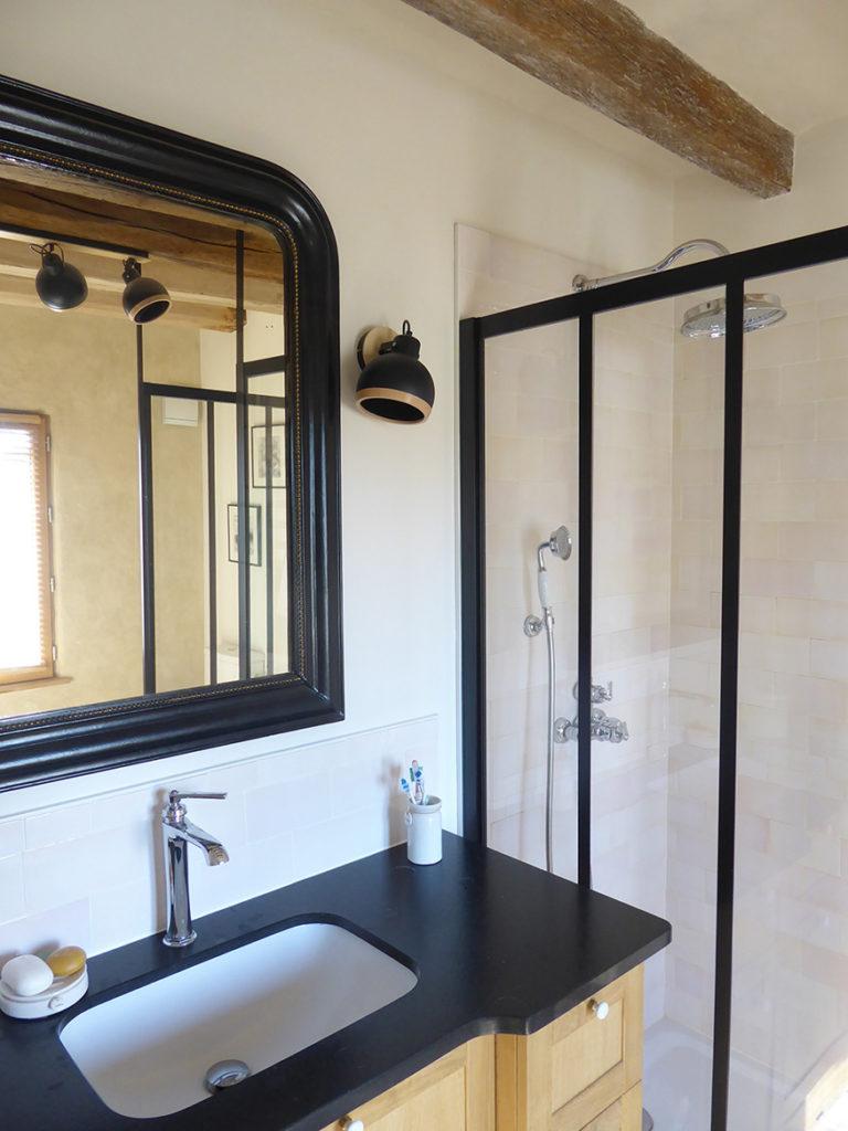 Une salle de bains restaurée avec un meuble vasque en beau granit noir